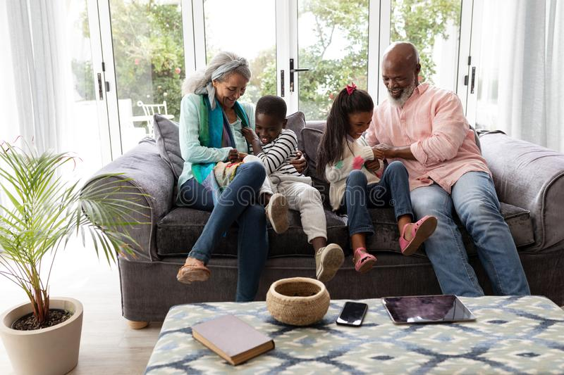 Multi-generation family having fun together on a sofa in living room. Front view of African american Multi-generation family having fun together on a sofa in stock image