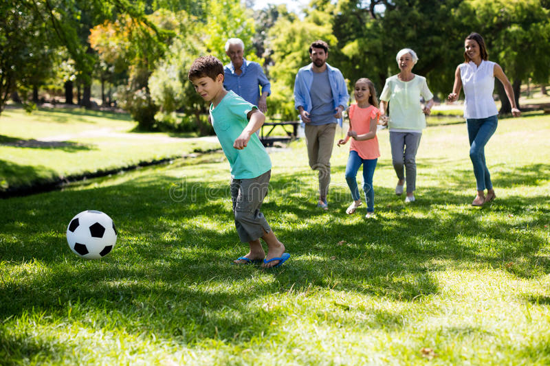 Multi generation family playing football in park royalty free stock image
