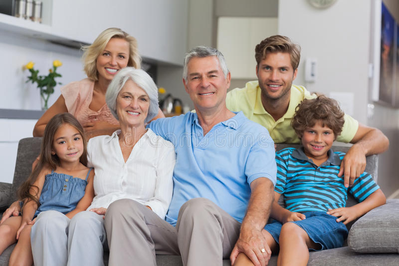 Multi-generation family posing in the living room stock images