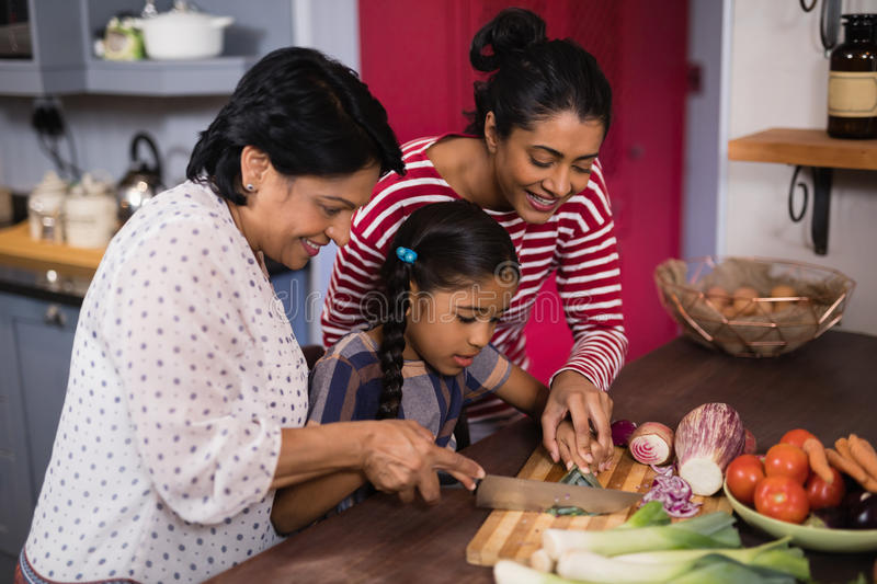 Multi-generation family preparing food together in kitchen stock photography