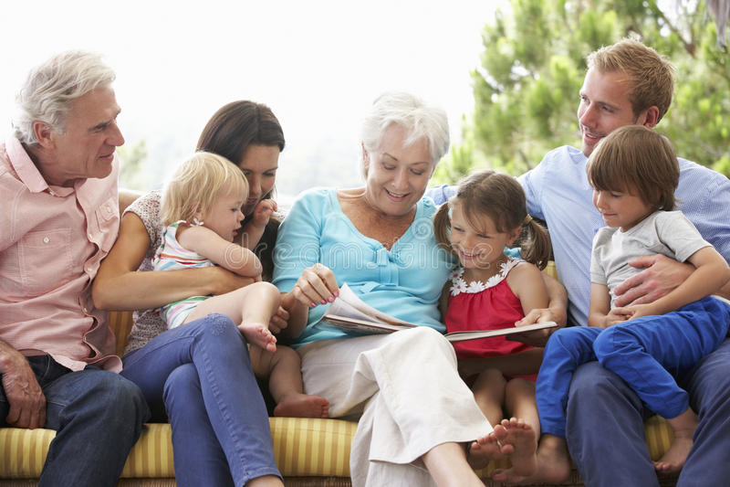 Multi Generation Family Reading Book On Garden Seat stock photography