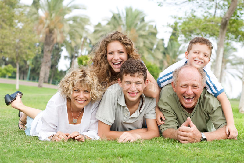 Multi-generation family relaxing in park stock photography