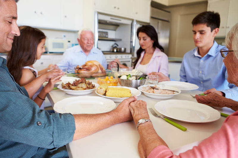 Multi-Generation Family Saying Prayer Before Eating Meal. Holding Hands With Eyes Closed stock image