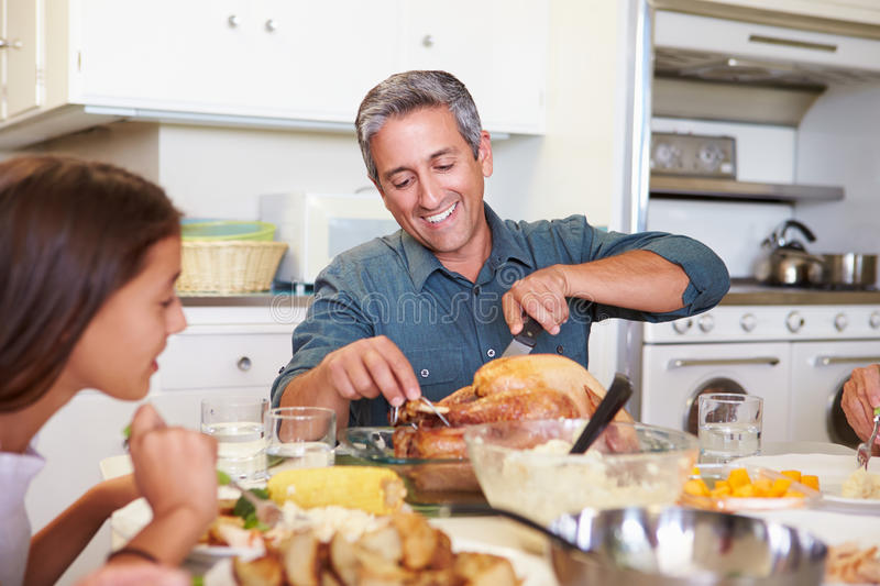 Multi-Generation Family Sitting Around Table Eating Meal. With Father Cutting Chicken stock photo