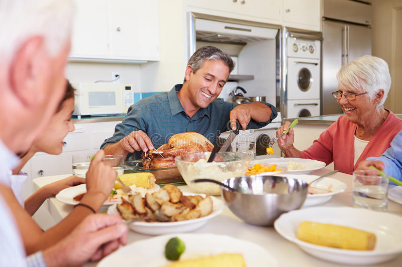 Multi-Generation Family Sitting Around Table Eating Meal. In Kitchen Smiling At Each Other royalty free stock photos