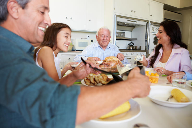 Multi-Generation Family Sitting Around Table Eating Meal. In Kitchen Smiling At Each Other royalty free stock image