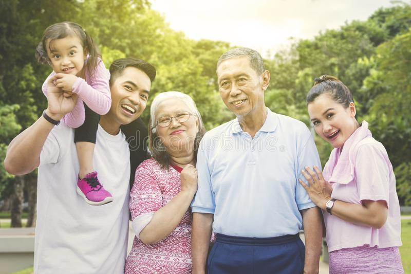 Multi generation family smiling in the park royalty free stock photography
