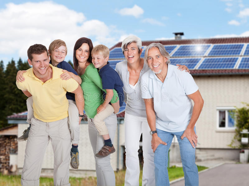 Multi generation family standing against house stock photo