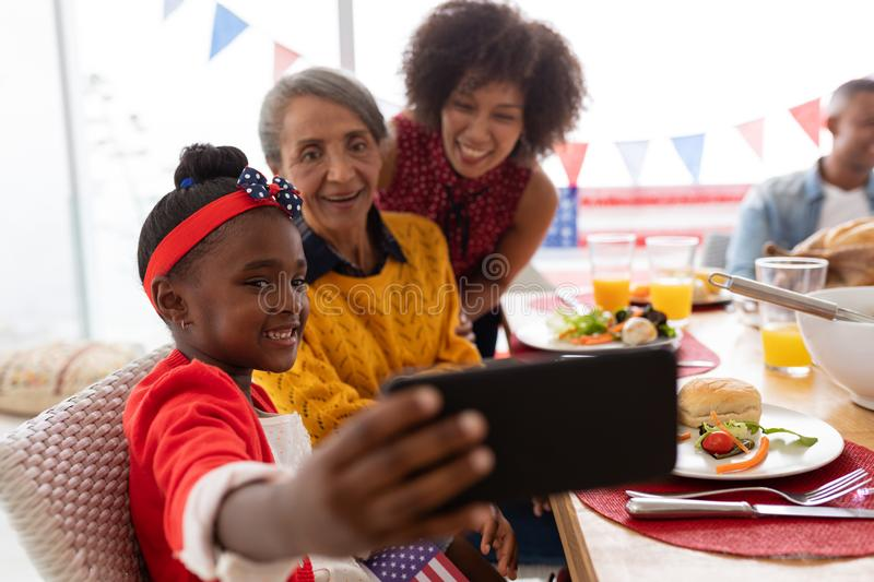 Multi-generation family taking selfie with having meal on a dining table stock image
