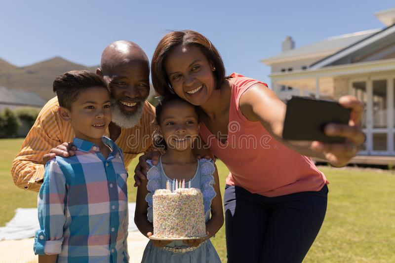 Multi-generation family taking selfie with mobile phone while celebrating birthday of grandaughter royalty free stock photography