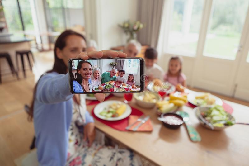 Multi-generation family taking selfie with mobile phone while having food on dining table stock photography