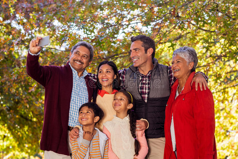 Multi-generation family taking selfie at park stock photography