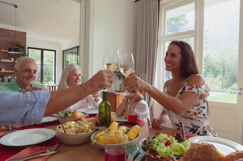 Multi-generation family toasting glasses of champagne on dining table at home royalty free stock image