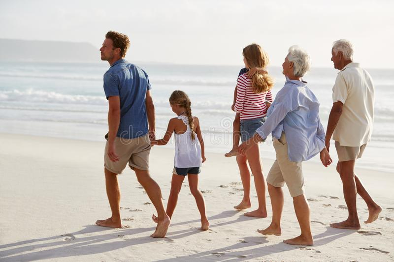 Multi Generation Family On Vacation Walking Along Beach Together royalty free stock photos