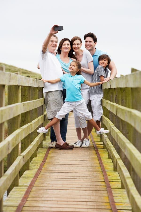 Multi Generation Family Walking On Bridge Taking Photo royalty free stock image