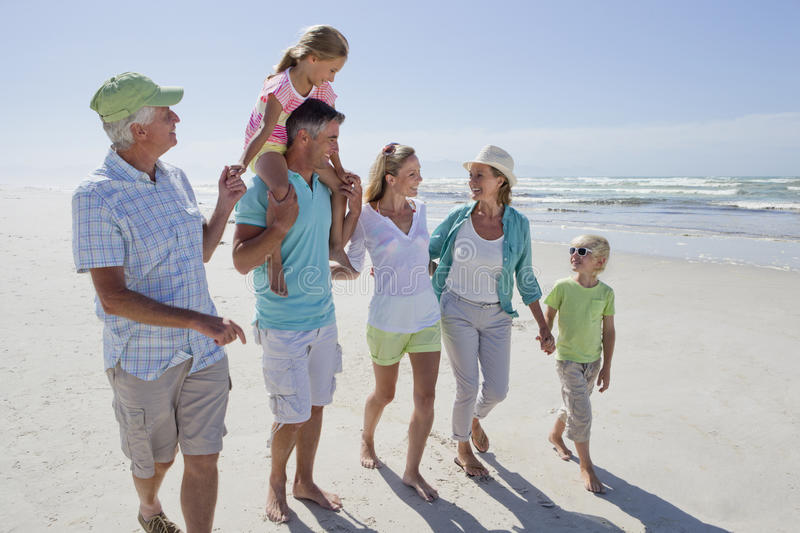 Multi-generation family walking on sunny beach royalty free stock photography