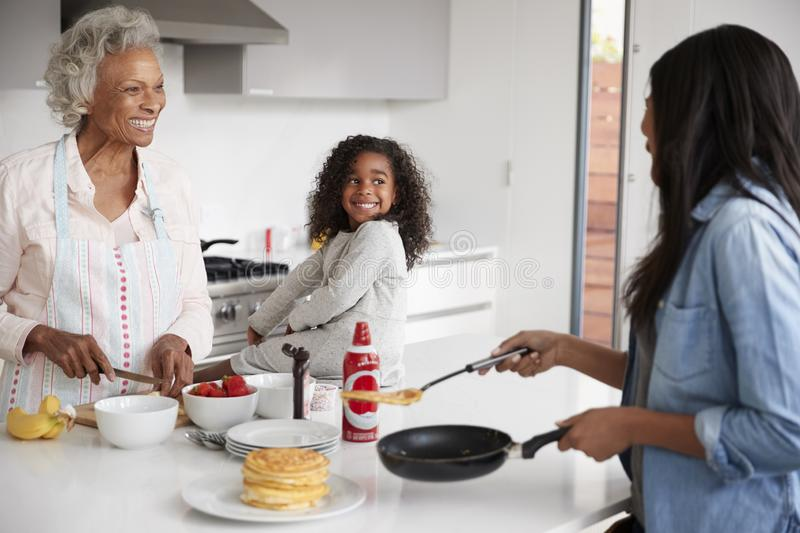Multi Generation Female Family In Kitchen At Home Making Pancakes Together stock photo