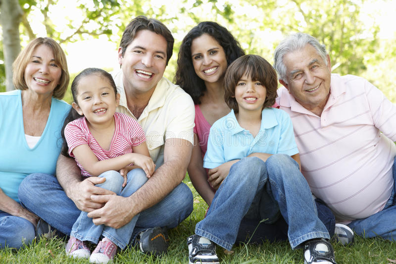 Multi Generation Hispanic Family Standing In Park stock images