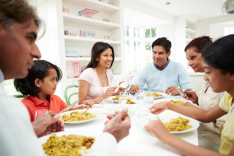 Multi Generation Indian Family Eating Meal At Home. Chatting To Each Other stock photos
