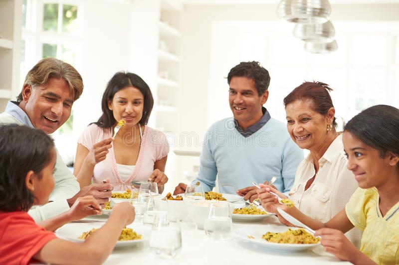 Multi Generation Indian Family Eating Meal At Home. Sitting At Table Chatting royalty free stock photography