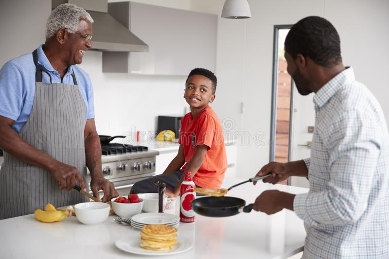 Multi Generation Male Family In Kitchen At Home Making Pancakes Together stock photos