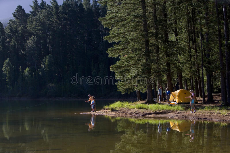 Multi-generational family on camping trip, boy (8-10) and grandfather fishing in lake in mid-distance, side view stock photography