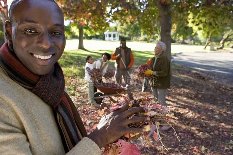 Multi-generational family collecting autumn leaves in garden, focus on father standing in foreground, portrait stock photography