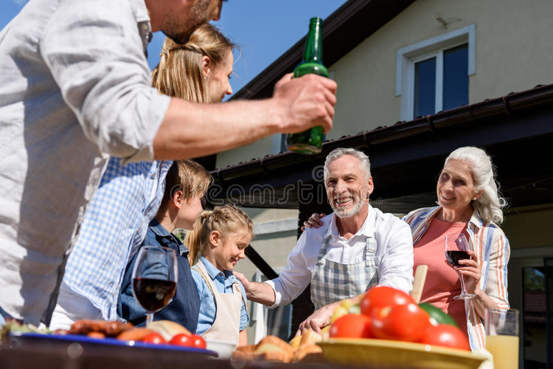 Multi-generational family having picnic on patio at daytime royalty free stock images