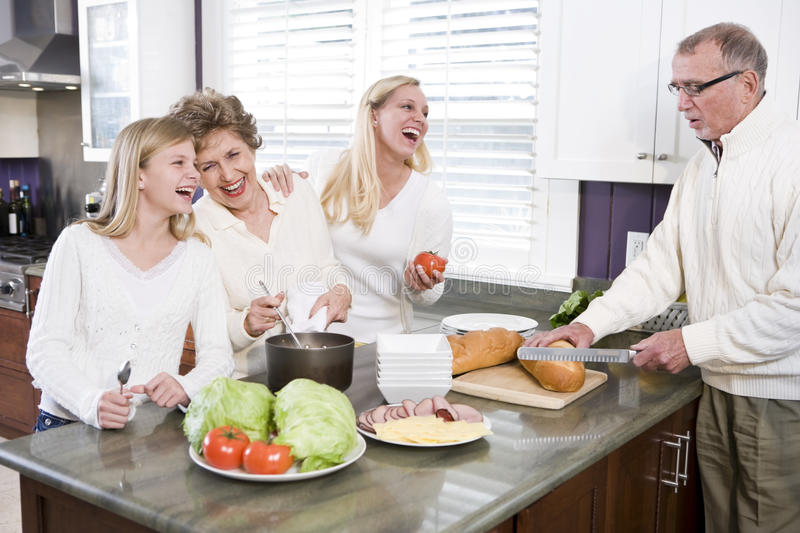Multi-generational family making lunch in kitchen stock photo