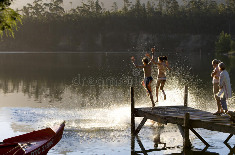 Multi-generational family standing on jetty at sunset, children (7-10) jumping into lake, side view royalty free stock photos