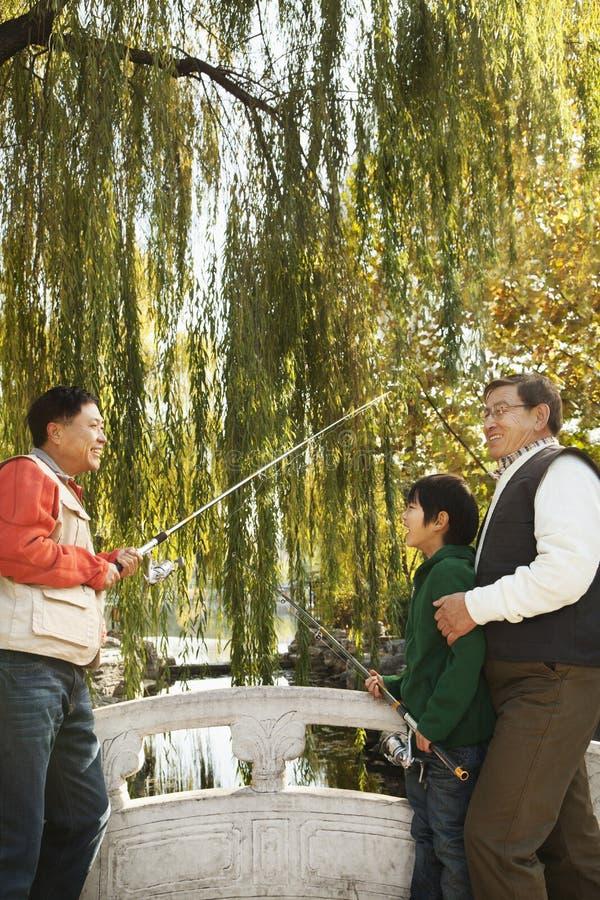 Multi-generational men fishing at lake royalty free stock photography