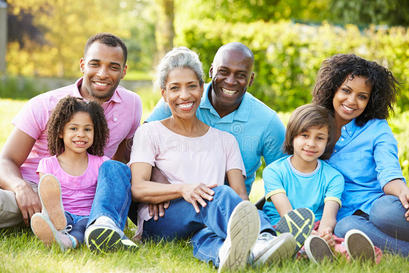 Multi Generations-Afroamerikaner-Familie, die im Garten sitzt stockbild