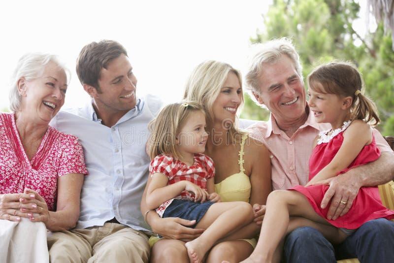 Multi Generations-Familie, die auf Garten Seat sitzt lizenzfreie stockfotos