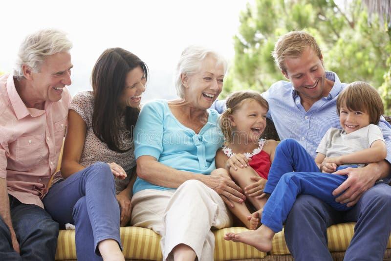 Multi Generations-Familie, die auf Garten Seat sitzt lizenzfreie stockfotografie