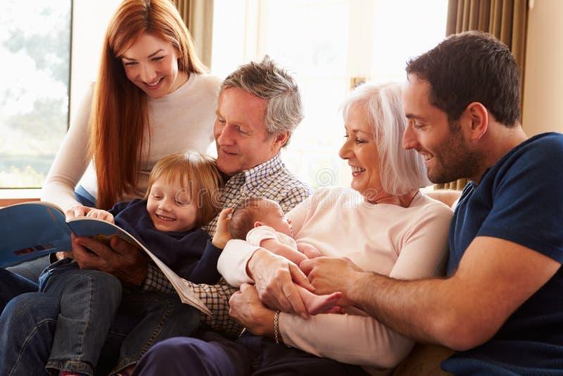 Multi Generations-Familie, die auf Sofa With Newborn Baby sitzt lizenzfreies stockbild