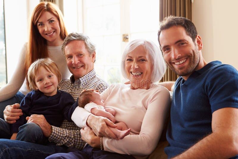 Multi Generations-Familie, die auf Sofa With Newborn Baby sitzt stockbild
