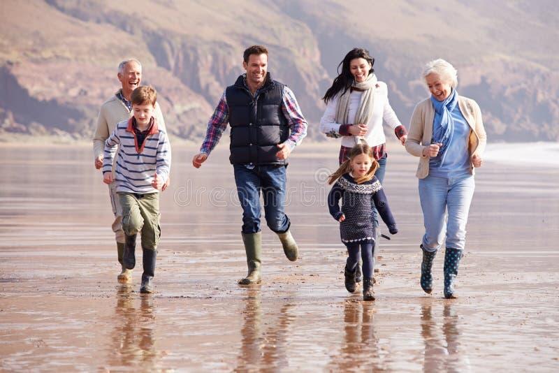Multi Generations-Familie, die auf Winter-Strand läuft lizenzfreie stockfotos