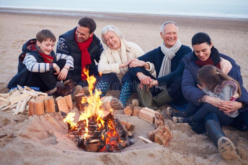 Multi Generations-Familie, die durch Feuer auf Winter-Strand sitzt lizenzfreies stockfoto
