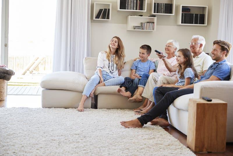Multi Generations-Familie, die im Sofa At Home Watching Fernsehen sitzt stockfotografie