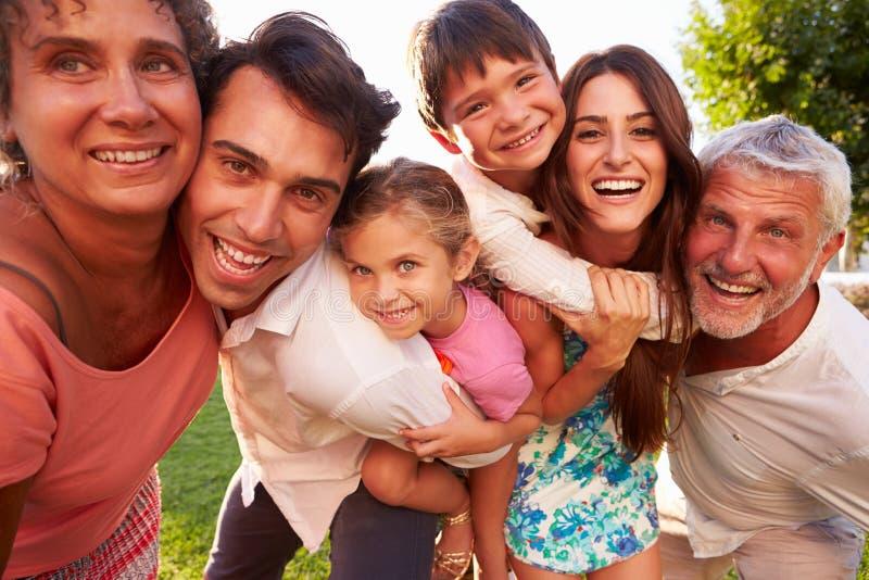 Multi Generations-Familie, die Kindern Doppelpol im Park gibt lizenzfreie stockfotografie