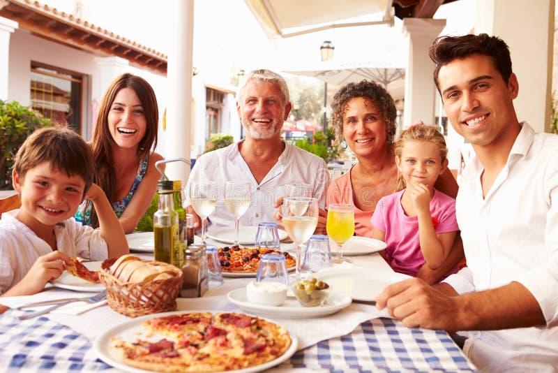 Multi Generations-Familie, die Mahlzeit Restaurant am im Freien isst lizenzfreie stockfotografie