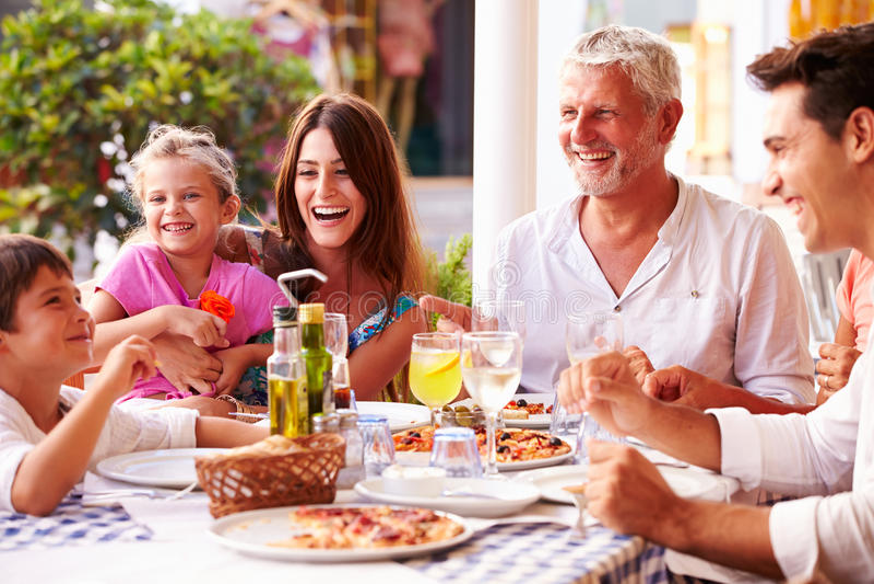 Multi Generations-Familie, die Mahlzeit Restaurant am im Freien isst stockfotografie