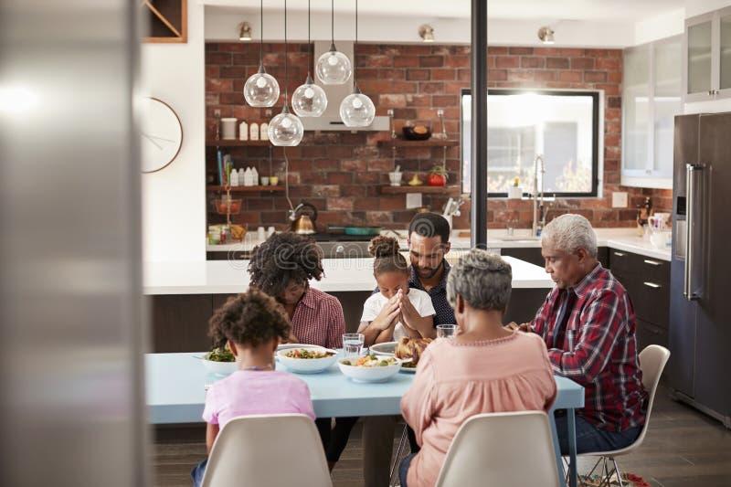 Multi Generations-Familie, die zu Hause vor Mahlzeit um Tabelle betet stockbild