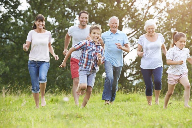 Multi Generations-Familie, die zusammen über Feld läuft lizenzfreie stockfotos