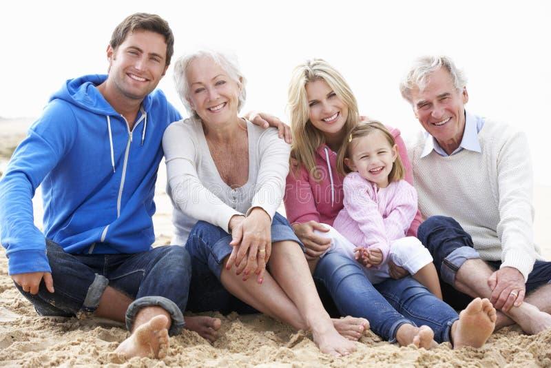 Multi Generations-Familie, die zusammen auf Strand sitzt stockbild