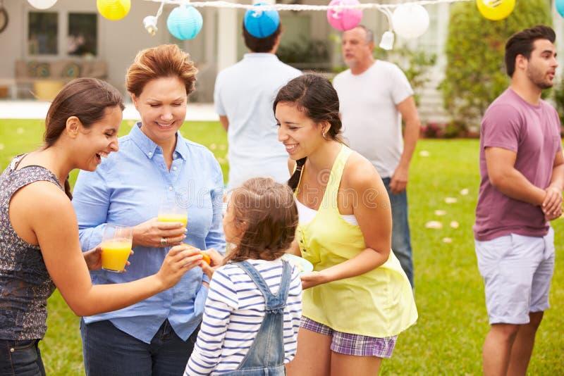 Multi Generations-Familie, die zusammen Partei im Garten genießt stockbilder