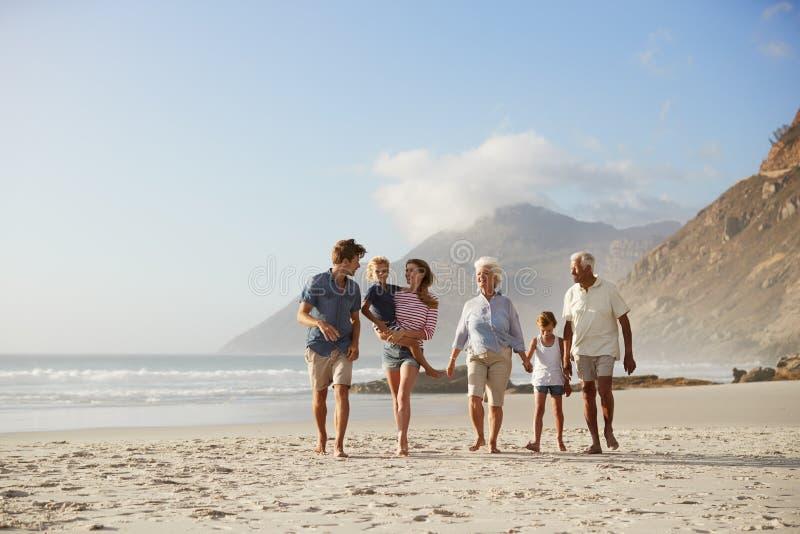 Multi Generations-Familie im Urlaub, die zusammen entlang Strand geht stockfoto