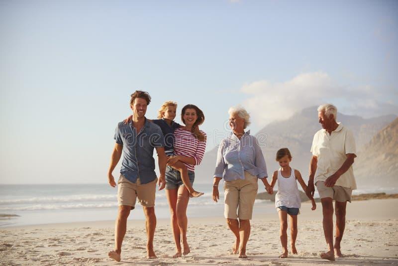 Multi Generations-Familie im Urlaub, die zusammen entlang Strand geht lizenzfreies stockbild