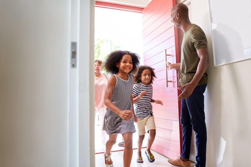Multi Generations-Familie mit den Großeltern, die zu Hause Enkelkinder besuchen lizenzfreie stockbilder
