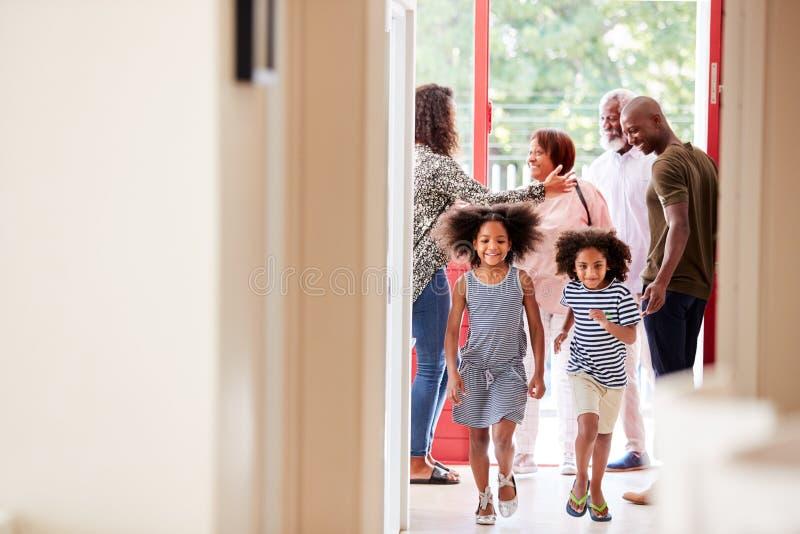 Multi Generations-Familie mit den Großeltern, die zu Hause Enkelkinder besuchen lizenzfreies stockfoto
